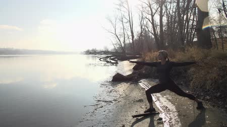 Wideshot of young beautiful female model doing yoga by a river on a cold autumn day.