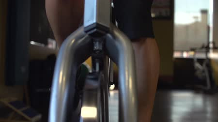 Sliding slow motion shot of female athlete riding an exercise bike in a gym.  Shot on a Sony FS700 at 240fps.