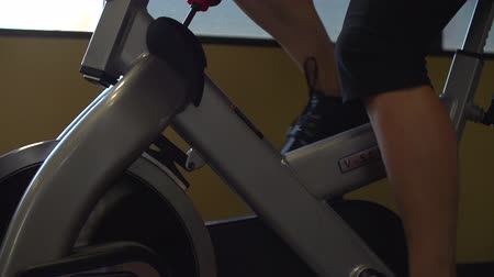Gliding shot of female fitness model riding an exercise bike inside a gym in slow motion.  Shot on a FS700 at 240fps.