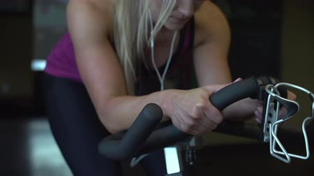 Dolly shot of beautiful blonde fitness model riding exercise bike showing her hands on the handles.