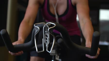 Dolly shot of beautiful toned female athlete riding exercise bike inside gym. Stok Video