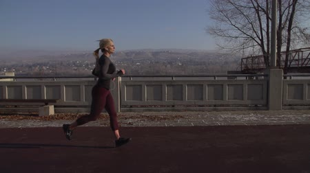 A female athlete runs along the river in slow motion.  Filmed at 240 fps with Sony FS700.