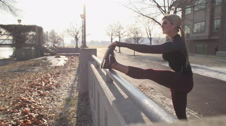 dech : Cinematic slider shot of beautiful blonde female runner stretching on a cold autumn day.