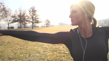 Fitness model completes yoga moves on a sunshine day in the park wearing headphones.