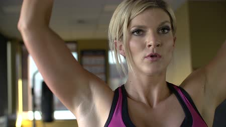 Close up of female athlete doing shoulder presses while looking in the mirror. Stok Video