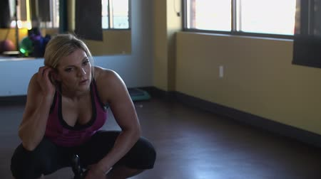 Female athlete crouches down and takes a breath. Stok Video