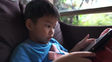 dragging : 4K little asian boy sitting on sofa using digital tablet play educaional online games at home. Looking at screen, hands moving and clicking on device.