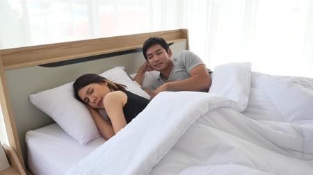 sulky : Young asian woman feeling angry and sulky, the man reconciling by touching her shoulder. Girlfriend avoiding boyfriends touch and looking away while lying in the bed. Family problems concepts.