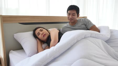 sulky : Asian woman feeling angry and sulky, the man apologizing for mistake. Asian couples reconcile in bedroom, family compromise and bridging the gap. Stock Footage