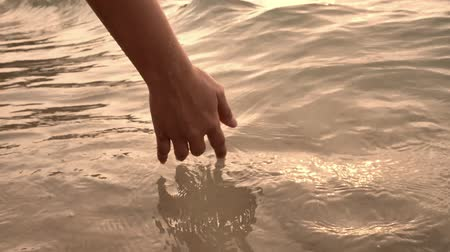 Close up of a womans hand is gently touching the clear surface water waves of the sea in sunset, Patttaya beach in Thailand, Asia. Slow motion video of happiness, holidays and relaxation concepts.