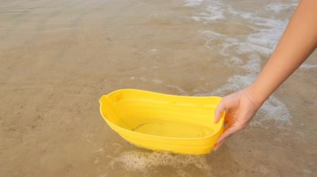 вред : Womans hand letting go a yellow toy boat in water of the sea or waves at Pattaya beach in Thailand, Asia. The boat floating on waves then flipped on its side. Hope, life insurance, crisis concepts.