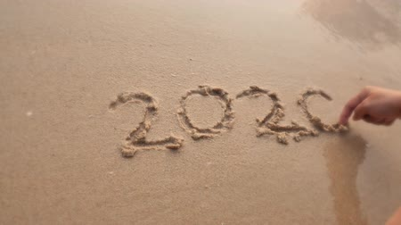 Goodbye 2020, lettering on beach was washed off by sea wave with sand background. Handwritten 2020 on beautiful sand beach in Asia. End of the year, new year, countdown and memory concepts.