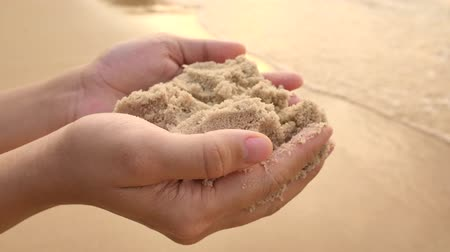 relieve : Adult female holding wet and soft sand in her hands on the beach at sunset. Summer holiday at Pattaya beach of Thailand, Asia. Vacations, relaxation, Zen and nature concepts. Stock Footage