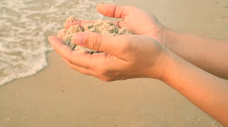 relieve : Womans hand holding wet sand and let it falling on the beach, beautiful sea on background. Traveler on sunset time of Pattaya beach in Thailand, Asia. Holiday, vacations, relaxation, nature concepts.
