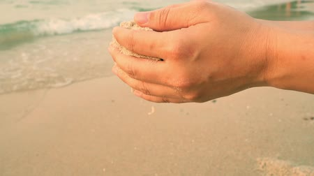 relieve : Slow motion shot of sand falling from hands back on the beach with beautiful sea on background. Summer holiday at  Pattaya beach of Thailand, Asia. Vacations, relaxation, Zen and nature concepts. Stock Footage