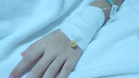 infusion : Close-up of hand bandaged of sick asian child girl with dehydration, receiving medication through intravenous fluid therapy, lying in hospital bed. Health insurance, treatment, medical concepts. Stock Footage