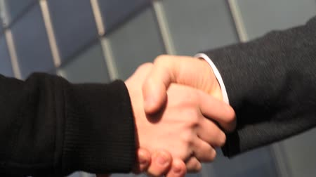 homem de negócios : Senior and young businessmen shaking hands in front of office building. Vídeos