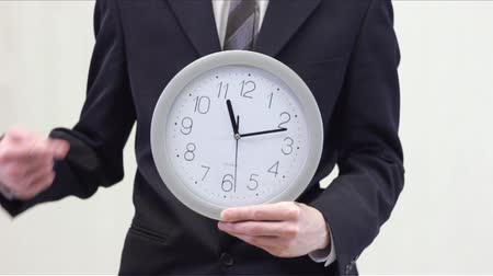 minute hand : Business man in suit holding classic mechanical watch in his hands and pointing at the time. Good video for Tv programs, documentary films, etc. Areas of use: time is money, late for work, out of time, punctuality and deadline, etc. Stock Footage