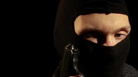 ladrão : Male murderer in balaclava mask in the darkness holding a gun and disappearing.