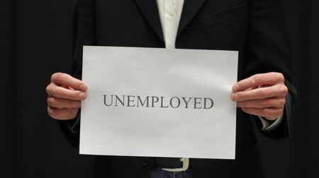 holding : Businessman tears up Unemployed sign