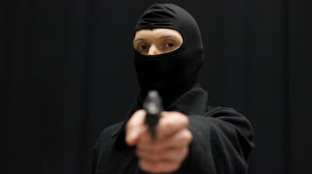 ladrão : Criminal in balaclava mask aiming at the viewer