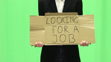 desemprego : Young unemployed business man with looking for a job sign