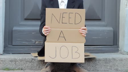 desemprego : Young Businessman with Need a Job sign begging in the street. People passing by.