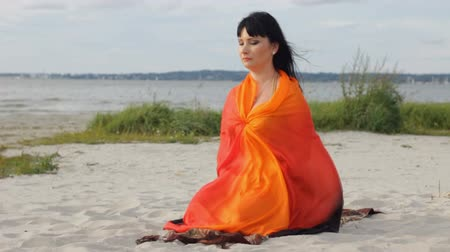 Young attractive woman meditation on a sunny seashore. Good illustrative clip about modern spiritual experience, enjoyment and medicine, harmony and tranquility.