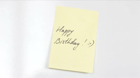 mensagem : Yellow sticker put on the door of refrigerator with happy birthday note and a smile.