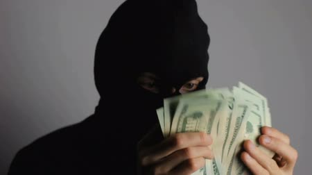 thieve : Criminal in mask counting dollars.