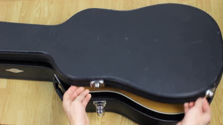 защелка : Musician opening guitar case.