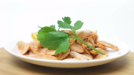 Shrimps with Slices of Lemon and Parsley Rotating on Wooden Plate