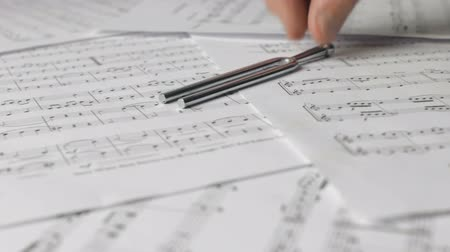 Placing metal tuning fork on sheet music
