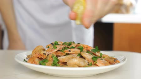 Chef squeezing fresh lemon over cooked shrimps
