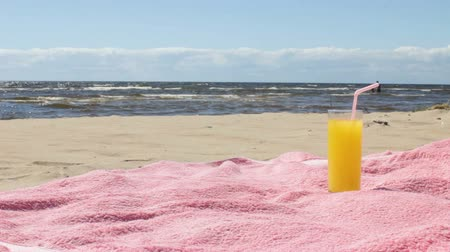 Glass of Juice on the Sunny Summer Beach