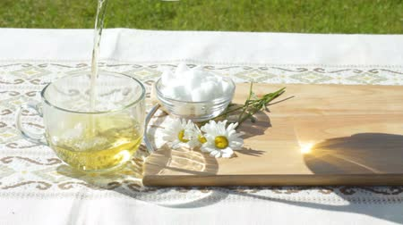 homeopati : Pouring chamomile tea outdoors Stok Video