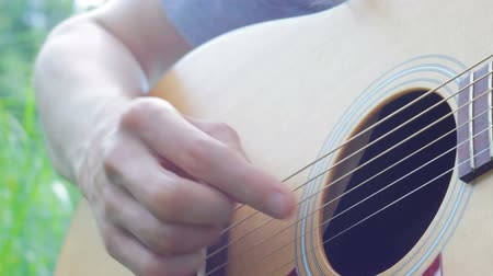 Musician playing acoustic guitar outdoors close up Vídeos