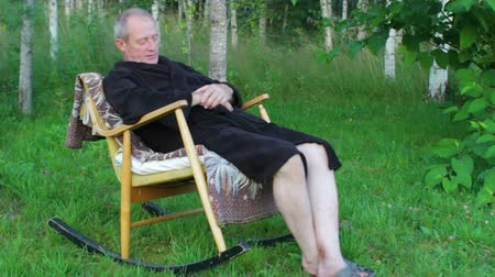 Senior Man in Bath Robe Sleeping in Rocking Chair Outdoors Vídeos