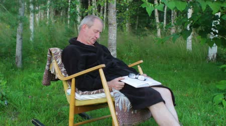 Senior Man in Bath Robe Sleeping in Rocking Chair Outdoors with Book in Hands Vídeos