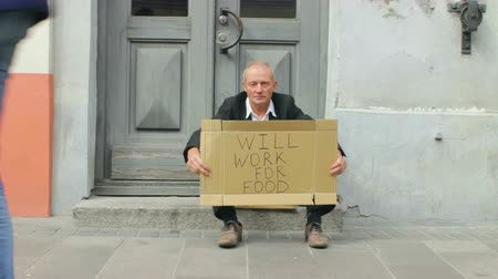 Destitute Bankrupt Businessman with Will Work For Food Sign in the Street