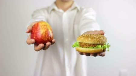 hamburgher : Man Weighting Healthy and Junk Food. Concetto di cibo sano e malsano