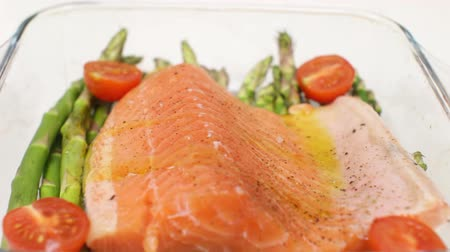 Pouring Olive Oil over Salmon and Asparagus