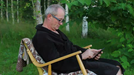Senior Man in Rocking Chair Using Tablet PC Outdoors Vídeos