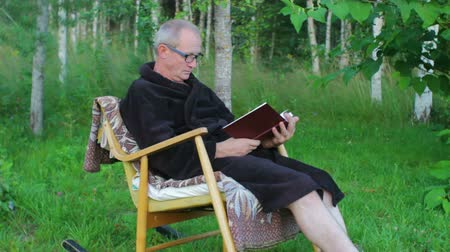 starszy pan : Senior Man Reading Outdoors in a Rocking Chair