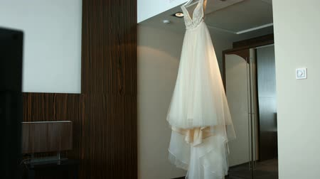 Wedding dress of the bride is hanging on