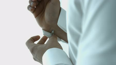 Groom wears stylish cufflinks close up