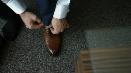 The man wears shoes. Tie the laces on the shoes. Mens style. To prepare for work, to the meeting.