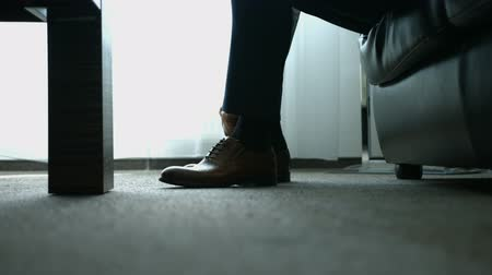 cadarço : The man wears shoes. Tie the laces on the shoes. Mens style. To prepare for work, to the meeting.