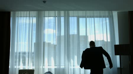 The man puts on his jacket in front of the window Stock Footage