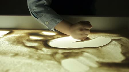 puericultura : hildren draw with their hands on the sand with illumination Stock Footage